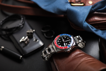mens accessories, closeup at wristwatch with black dial blue-red bezel and stainless steel bracelet.
