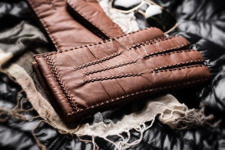 Pair of men's brown leather gloves and other men's accessories.