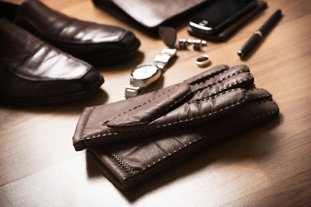 Pair of mens brown leather gloves and other mens accessories on the floor.
