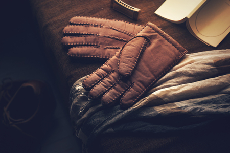 Pair of mens brown leather gloves and other mens accessories. Imagens