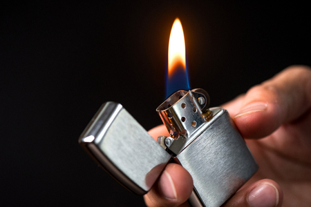 The man holding brushed chrome lighter with windproof in hand.
