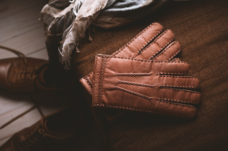 Pair of mens brown leather gloves and other mens accessories. Фото со стока