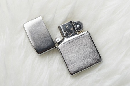 brushed chrome lighter with windproof isolated over white fur.