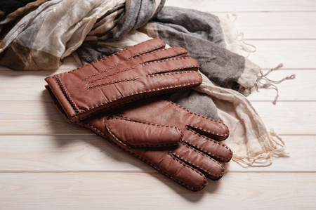 Pair of mens brown leather gloves and other mens accessories on wood background.