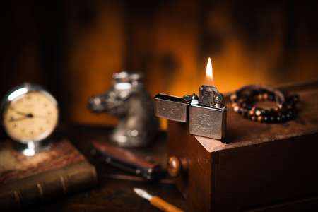 Burning brushed chrome lighter with windproof on the wooden desk. One of everyday carry item for men.