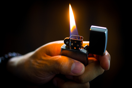 The man holding Brushed chrome lighter with windproof in the dark.