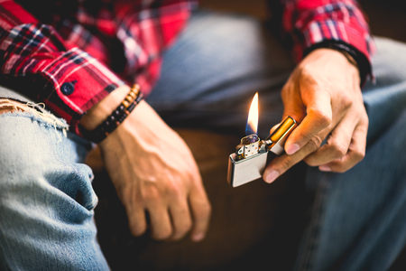 A man holding the burning brushed chrome lighter with windproof. Stock Photo