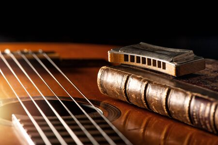 vintage wooden harmonica lying on an old acoustic guitar. 免版税图像