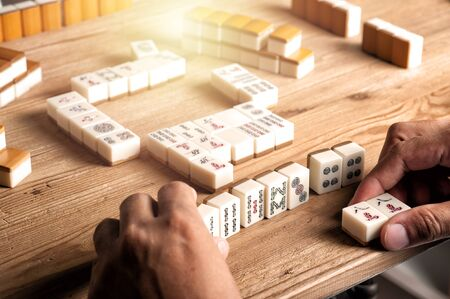 Playing Mahjong on wooden table. Mahjong is the ancient asian board game. 免版税图像