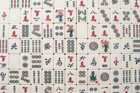 Many old mahjong tiles on wooden table. Mahjong is the ancient asian board game.