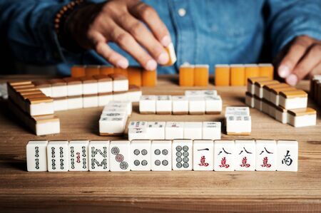 Playing Mahjong on wooden table. Mahjong is the ancient asian board game.