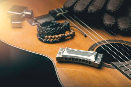 vintage wooden harmonica lying on an old acoustic guitar. 写真素材