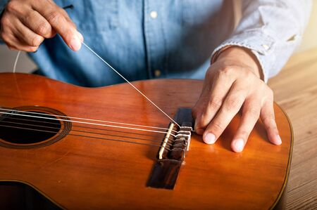 closeup mans hand changing strings on his old acoustic guitar.