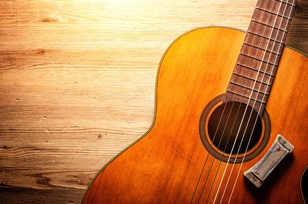 closeup classical guitar with harmonica over wood background