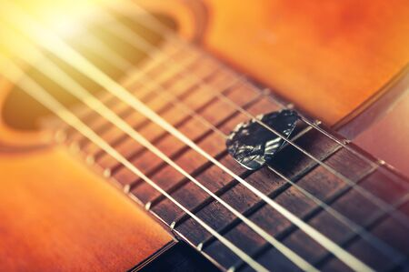 Closeup guitar pick on an old classical guitar. A guitar pick is a plectrum used for guitars. Stock Photo