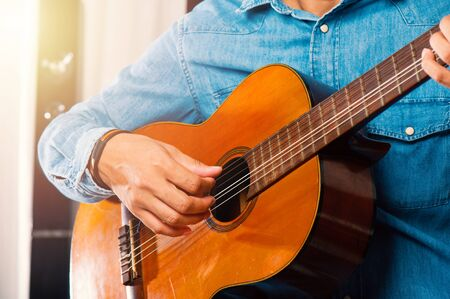 closeup mans hand playing his old classical guitar.