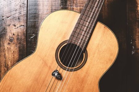 classical guitar with guitar pick on wooden background 写真素材