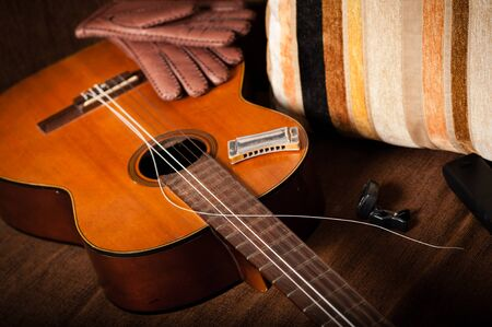 vintage classical guitar with broken string on the sofa.