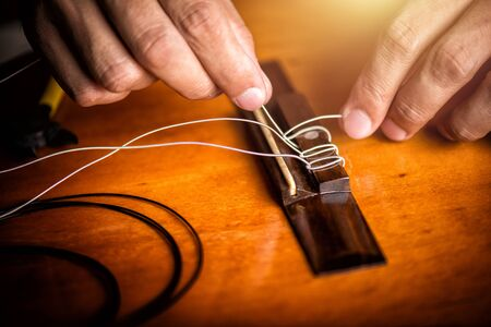 Restring classical guitar concept. The man restring his classical guitar.