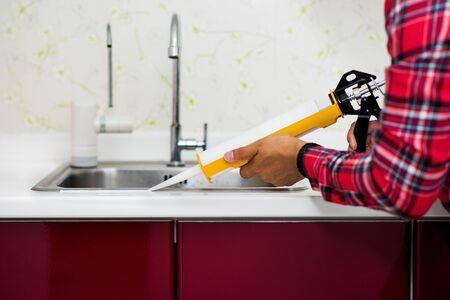 L'homme appliquant du mastic silicone. L'homme réparant la maison.