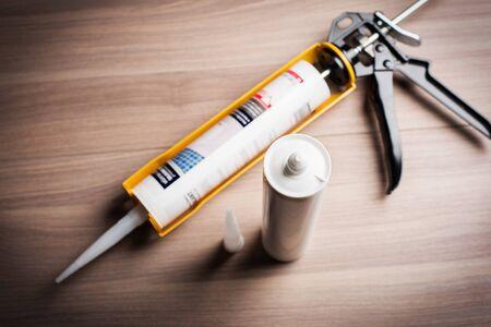 weiße Silikon-Dichtstoffkartusche und gelb-schwarze Dichtstoff-Pistole