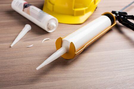 white silicone sealant cartridge and yellow-black sealant gun Фото со стока - 132852011