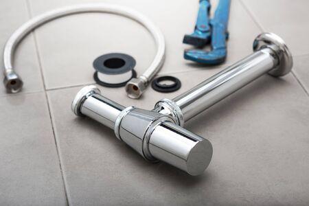 nouveau siphon en métal et autres équipements d'évier dans la salle de bain.