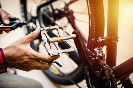 L'homme changeant les pédales de vélo. Concept de mise à niveau du vélo de montagne.