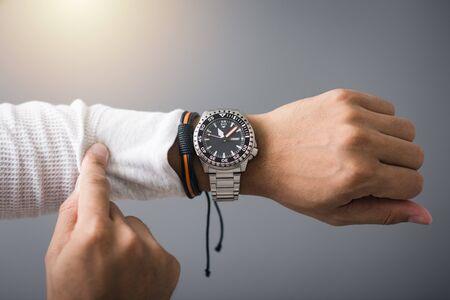 Closeup Luxus Herrenuhr mit schwarzem Zifferblatt und Edelstahlarmband am Handgelenk des Menschen.