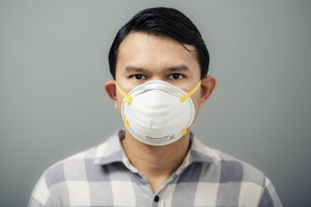 Portrait of asian man wearing N95 mask to against PM 2.5 air pollution. Stock Photo