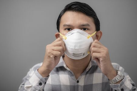 Portrait of asian man wearing N95 mask to against PM 2.5 air pollution.