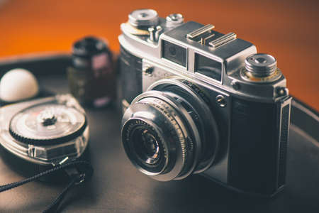 Old film camera with film and light meter. Stock Photo