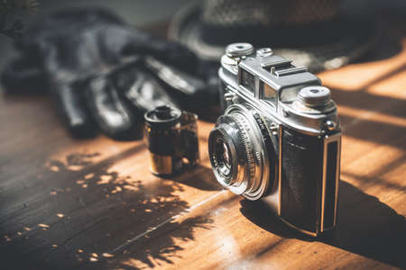 Old film camera on wooden desktop.