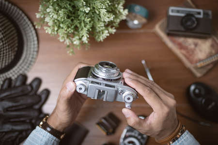 Photographer holding vintage camera in his hand over the desktop.