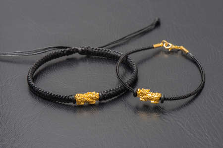 Wealth PiXiu bracelet, closeup at the gold PiXiu. PiXiu is a Chinese mythical auspicious creature, also known as PiYao.