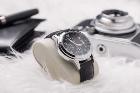 Men accessories on white background. Closeup at luxury men watch with black dial and leather strap.