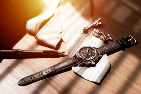 Closeup at luxury men wristwatch with black dial and leather strap. Men wristwatch on the wooden desktop.