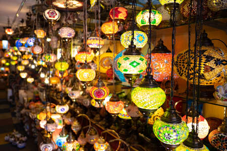 Colorful Turkish lamps and lanterns hanging in a lamp shop for sale.