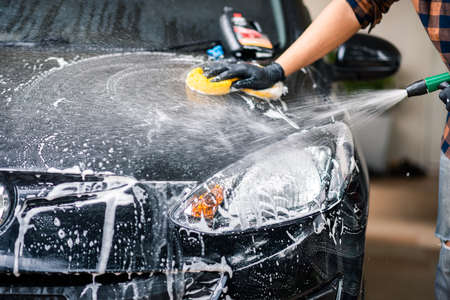 Washing the black car. Car cleaning and car care concept.