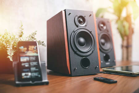 Playing song on speaker from smartphone. Home entertainment concept.