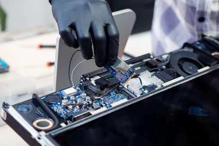 Technician reparing a broken computer. Computer service and repair concept.
