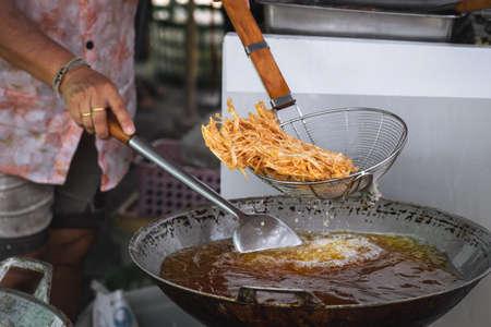 Frying shredded taro in hot oil. Cooking crispy shredded taro, vegetarian food. 免版税图像 - 166344468