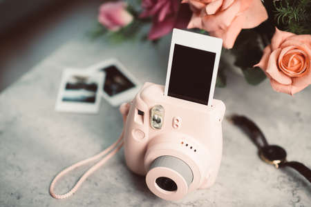 The pink instant camera with blank instant films.