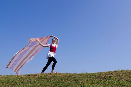 happy young girl run while holding the scarf with blue sky background photo