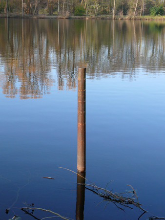 Rusted poller in the lake Stockfoto