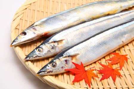 Saury and maple leaves on bamboo basket photo