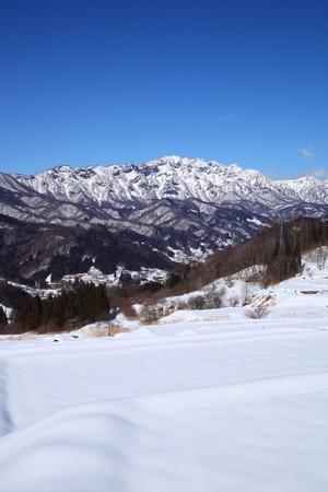 Snow covered field and Mt Togakushi, Nagano Japan photo