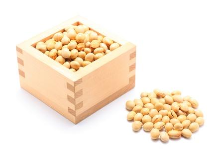 白い背景の上木製の正方形のカップの大豆
