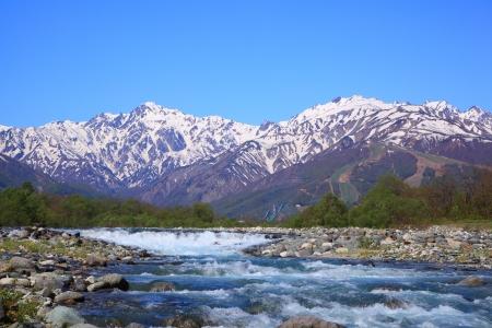 early spring snow: Mt  Goryudake and Matsukawa River in Hakuba Village, Nagano, Japan Stock Photo