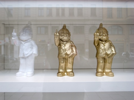 humorously: berlin,germany,20 february  2011:three dwarfs are placed on display to the outside, they humorously show the middle finger to people who stop front of the window.